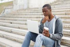 Uomo di colore pensieroso che per mezzo del computer portatile all'aperto Immagine Stock