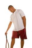 Uomo di colore in racchetta di tennis bianca della holding della camicia fotografie stock libere da diritti
