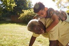 Uomo di colore senior con il nipote che guida sul suo indietro immagine stock libera da diritti