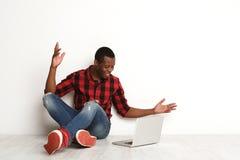 Uomo di colore sorridente che per mezzo del computer portatile che si siede sul pavimento dello studio Fotografia Stock