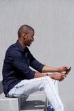 Uomo di colore sorridente che si siede sui punti che esaminano compressa digitale Fotografie Stock