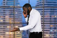 Uomo di colore sorridente con il telefono Immagine Stock