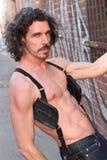 Uomo di cuoio muscolare che sta in ingranaggio del feticcio fotografie stock