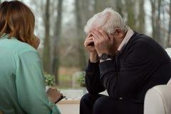 Uomo di disperazione durante la terapia psicologica fotografie stock