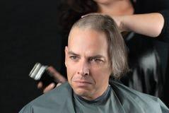 Uomo di dolore che ottiene capelli lunghi rasi fuori per la raccolta fondi del Cancro Immagini Stock Libere da Diritti