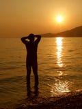 Uomo di felicità sul tramonto in mare Fotografia Stock Libera da Diritti