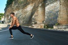 Uomo di forma fisica che allunga corpo, esercitantesi prima dell'correre all'aperto Immagine Stock Libera da Diritti