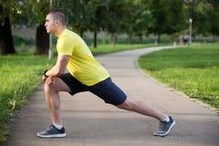 Uomo di forma fisica che allunga la spalla del braccio prima dell'allenamento all'aperto Atleta maschio sportivo in uno scaldarsi Fotografia Stock