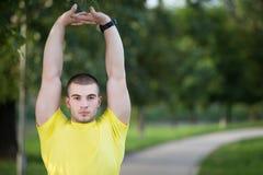 Uomo di forma fisica che allunga la spalla del braccio prima dell'allenamento all'aperto Atleta maschio sportivo in uno scaldarsi Fotografie Stock
