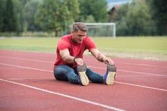 Uomo di forma fisica che allunga prima del funzionamento di allenamento sulla pista Immagini Stock Libere da Diritti