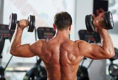 Uomo di forma fisica che fa allenamento del tricipite e della spalla Fotografia Stock