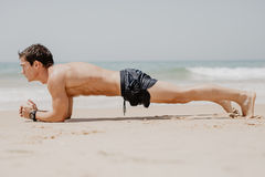 Uomo di forma fisica che fa esercizio di flessione sulla spiaggia Il ritratto del tipo di misura che risolve il suo il centro dei Fotografie Stock