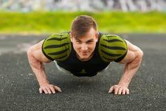 Uomo di forma fisica che fa spinta-UPS nello stadio, allenamento di addestramento trasversale Addestramento maschio sportivo fuor Fotografie Stock
