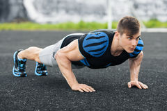 Uomo di forma fisica che fa spinta-UPS nello stadio, allenamento di addestramento trasversale Addestramento maschio attivo Immagine Stock