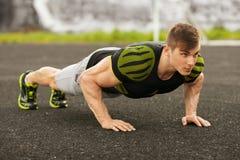 Uomo di forma fisica che fa spinta-UPS nello stadio, allenamento di addestramento trasversale Addestramento maschio sportivo fuor Immagini Stock