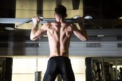 Uomo di forma fisica che fa tirata-UPS in una palestra per un allenamento posteriore Fotografia Stock