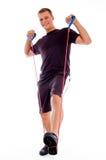 Uomo di forma fisica che propone con l'allungamento della corda Fotografia Stock