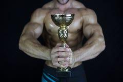 Uomo di forma fisica che riceve con la tazza di conquista Immagine Stock