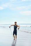 Uomo di forma fisica che si esercita alla spiaggia, facente esercizio dell'estensore all'aperto Fotografia Stock