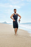 Uomo di forma fisica che si esercita alla spiaggia, facente esercizio dell'estensore all'aperto Fotografia Stock Libera da Diritti