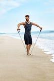 Uomo di forma fisica che si esercita alla spiaggia, facente esercizio dell'estensore all'aperto Immagini Stock