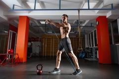 Uomo di forma fisica che si esercita con l'allungamento dell'elastico elastico nella palestra Fotografie Stock Libere da Diritti