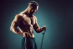 Uomo di forma fisica che si esercita con l'allungamento della banda Gli sport muscolari equipaggiano l'esercitazione con l'elasti Immagine Stock Libera da Diritti