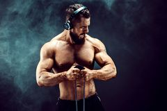 Uomo di forma fisica che si esercita con l'allungamento della banda Gli sport muscolari equipaggiano l'esercitazione con l'elasti Immagine Stock