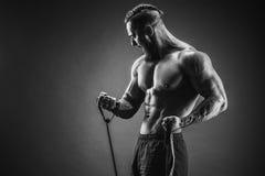 Uomo di forma fisica che si esercita con l'allungamento della banda Uomo muscolare di sport Fotografia Stock
