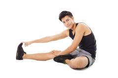 Uomo di forma fisica che si siede e che fa allungamento Fotografia Stock