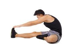 Uomo di forma fisica che si siede e che fa allungamento Fotografie Stock