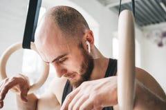 Uomo di forma fisica in cuffie senza fili che sembrano stanche dopo l'allenamento intenso immagine stock libera da diritti
