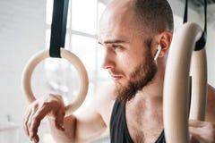 Uomo di forma fisica in cuffie senza fili che sembrano stanche dopo l'allenamento intenso fotografia stock libera da diritti