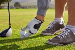 Uomo di golf che colloca sul tee su Fotografie Stock Libere da Diritti