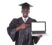 Uomo di graduazione con il computer portatile Fotografia Stock