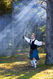 Uomo di grido in costume scozzese con la spada Immagini Stock Libere da Diritti