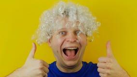 Uomo di grido riccio con emozione divertente e allegramente umana dei capelli bianchi, pollici su, sul fondo giallo della parete video d archivio