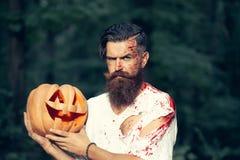 Uomo di Halloween con la zucca ed il sangue Fotografia Stock