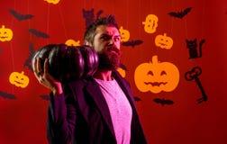 Uomo di Halloween con la zucca nell'oscurit? Witcher diabolico con capelli rossi e una barba in un mantello nero che legge un lib fotografia stock libera da diritti