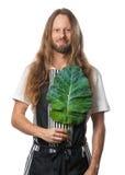 Uomo di hippy che tiene una foglia del cavolo sopra il suo cuore Fotografie Stock Libere da Diritti