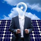 Uomo di idea con la condizione capa della lampadina davanti ad un pannello solare e un cielo blu e un sole Fotografia Stock Libera da Diritti