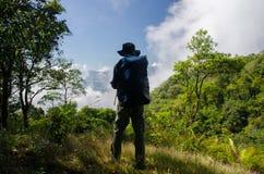 Uomo di immagine dell'alpinista che cammina sulla foresta profonda Fotografie Stock