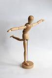 Uomo di legno del burattino che fa le esercitazioni Fotografia Stock