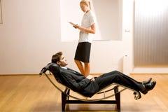 Uomo di lettura della donna che si trova sul longue del chaise Immagine Stock