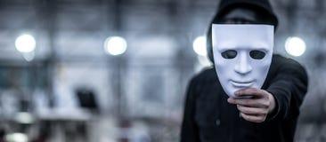 Uomo di maglia con cappuccio di mistero che tiene maschera bianca fotografie stock libere da diritti