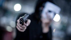 Uomo di maglia con cappuccio di mistero nella maschera bianca che indica pistola Concetti di violenza e di crimine Fuoco sulla pi fotografie stock libere da diritti