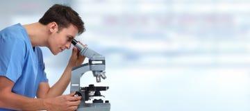 Uomo di medico con il microscopio Immagini Stock