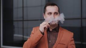Uomo di mezza età che fuma sigaretta elettronica all'aperto archivi video