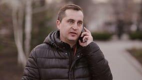 Uomo di mezza età che parla sul telefono sulla via in autunno stock footage