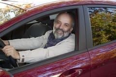 Uomo di mezza età che conduce un'automobile fotografia stock